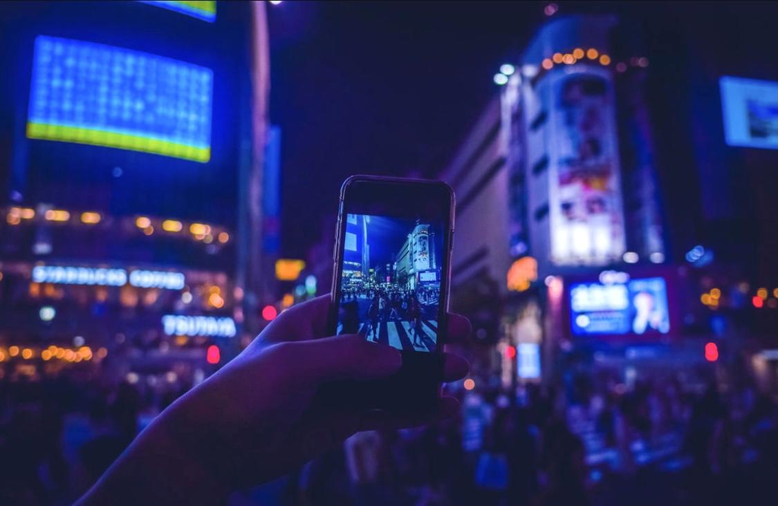 夜の東京の街で写真撮影をする男性。スマートフォンで写真や動画を撮影。ストックフォトあ